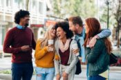 diverse group of millennials on a city street drinking coffee and laughing