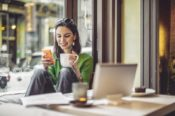 woman drinking coffee and looking at phone with laptop on table