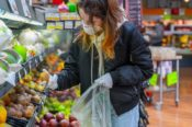 woman shopping for produce fruit wearing surgical mask and rubber gloves