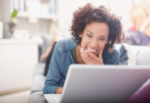 young smiling african-american woman looking at laptop