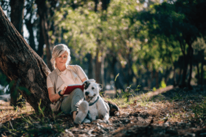 Woman sitting against tree reading