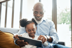 senior man and young girl looking at tablet